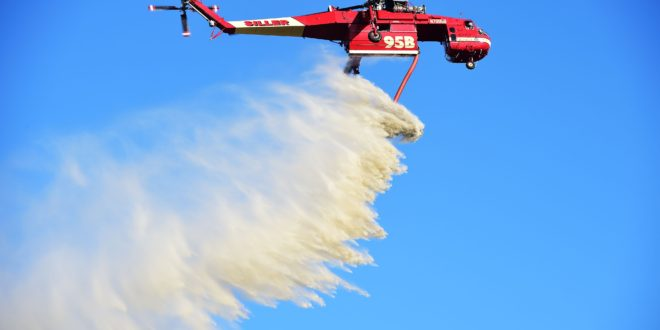 Taking advantage of low winds a helicopter drops water over farms and residences affected by the Lilac Fire, December 8, 2017, in Bonsall, California. Hot and dry Santa Ana winds have ignited wildfires across Southern California. / AFP PHOTO / Robyn Beck
